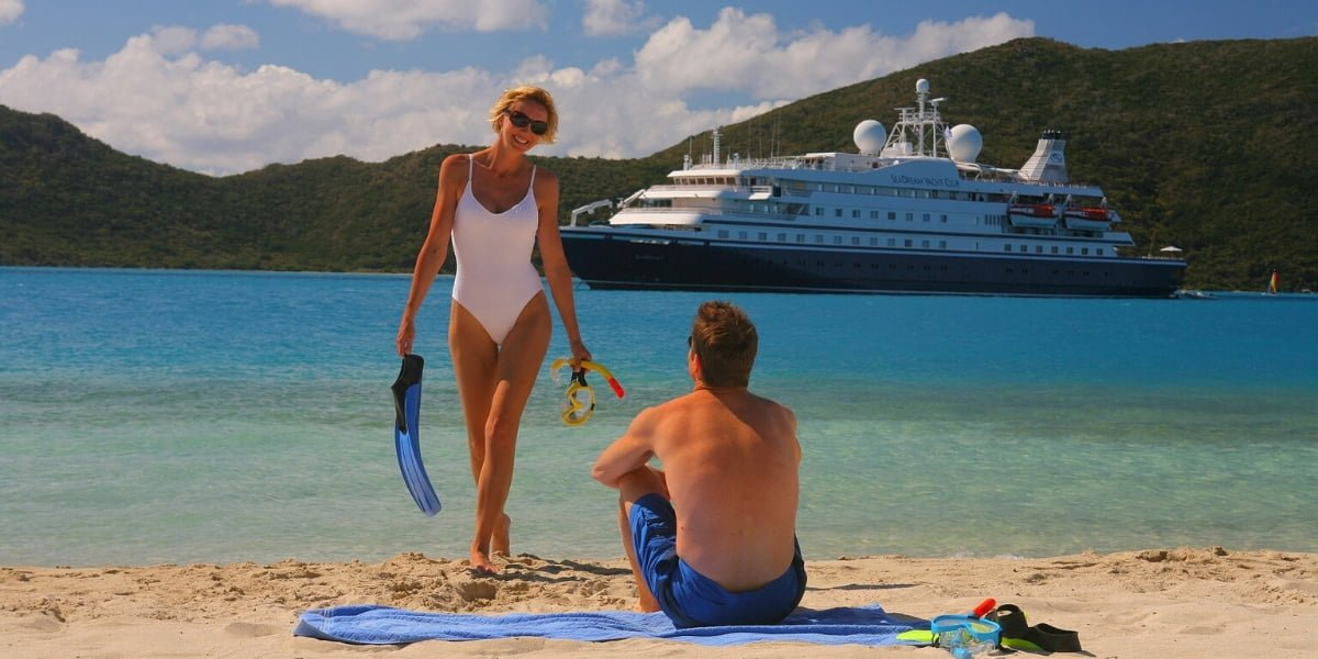 Man and woman on beach with cruise ship in background