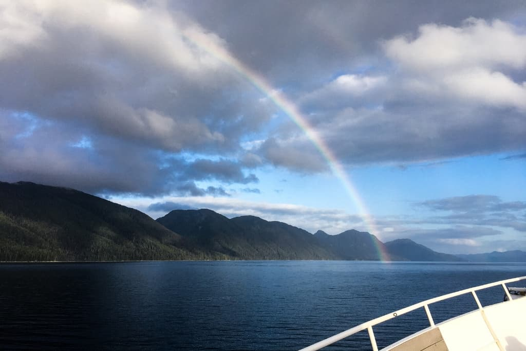 Rainbow over mountains and Glacier Bay from deck of UnCruise ship in Alaska