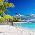 Caribbean beach with palm tree and cruise ship