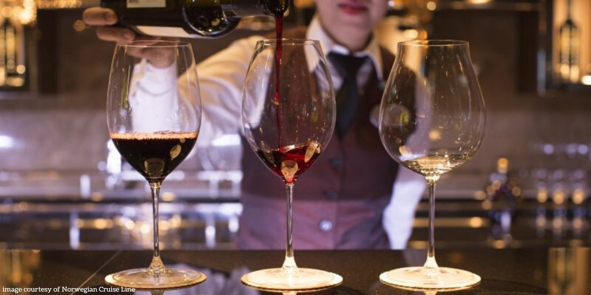 A Norwegian Cruise Line bartender pouring wine