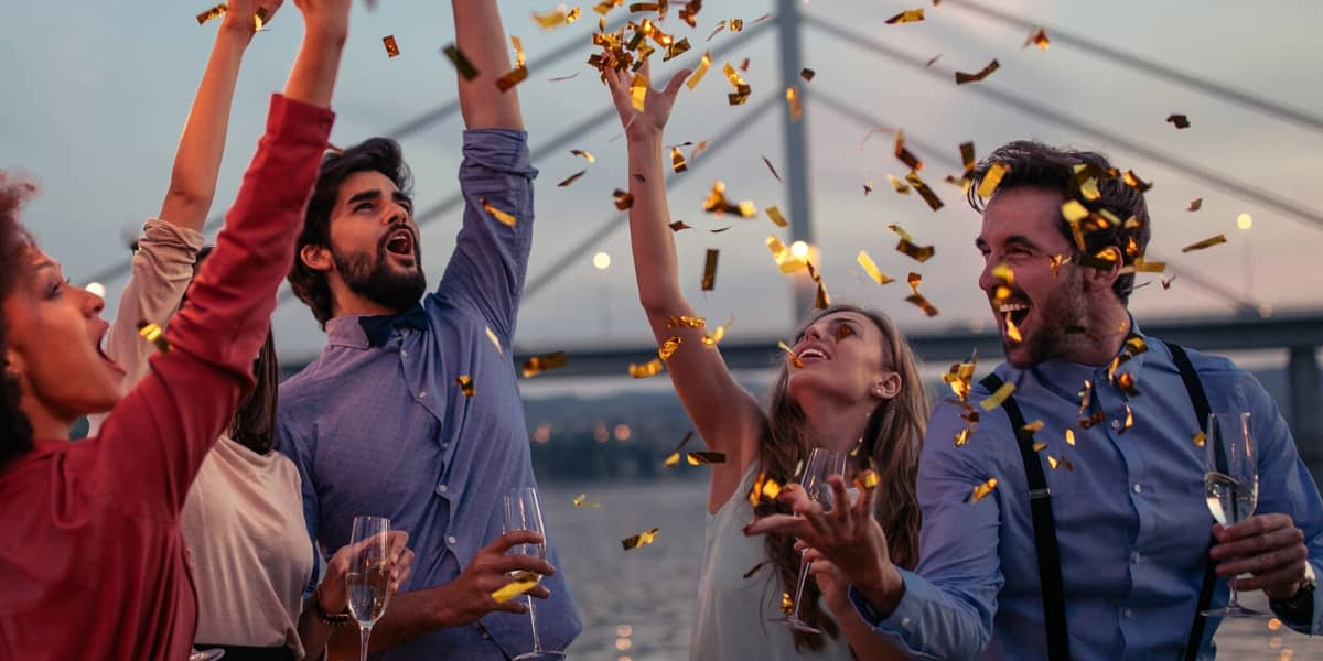 People drinking and throwing confetti on a cruise