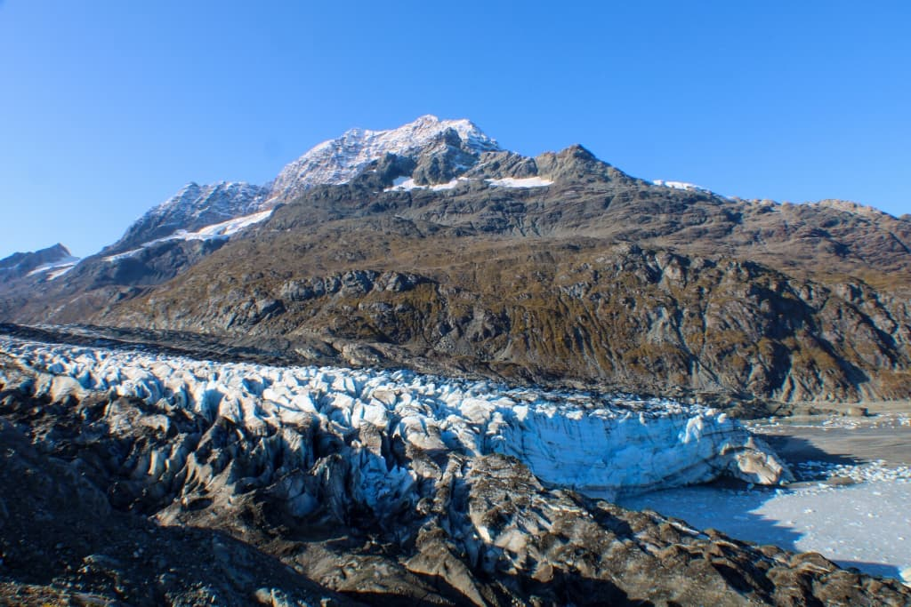 crevasses in the ice of Lamplugh Glacier with mountains and blue sky in the background