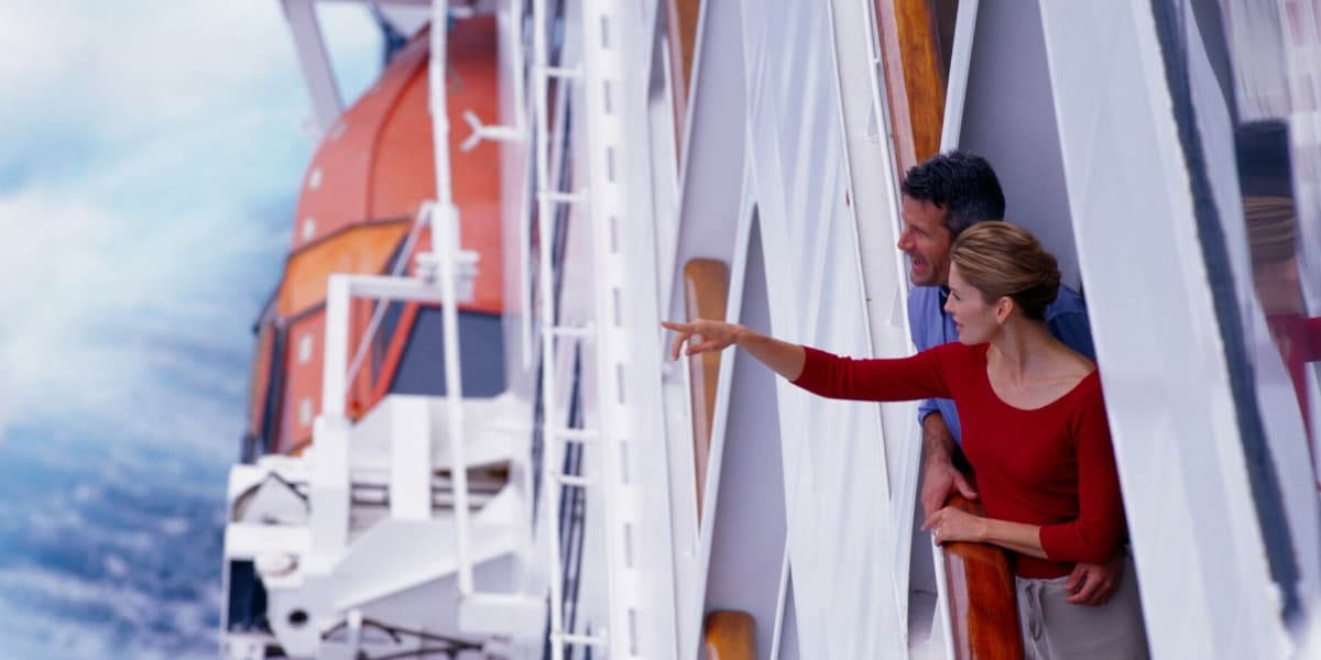 Man and woman looking out at ocean from cruise ship balcony