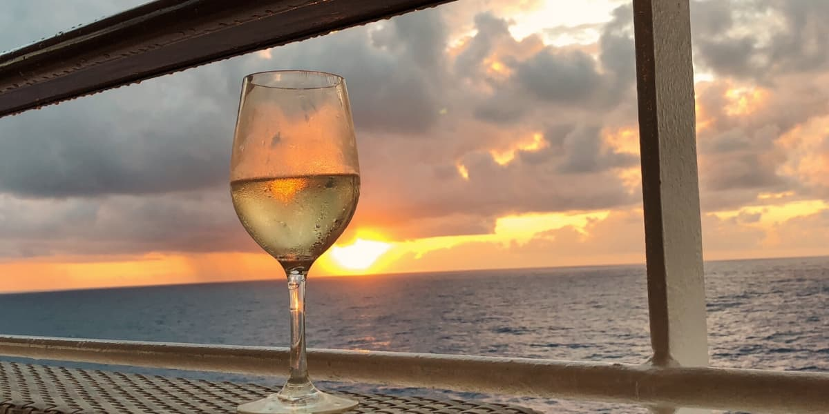 Glass of white wine by a cruise ship railing at sunset