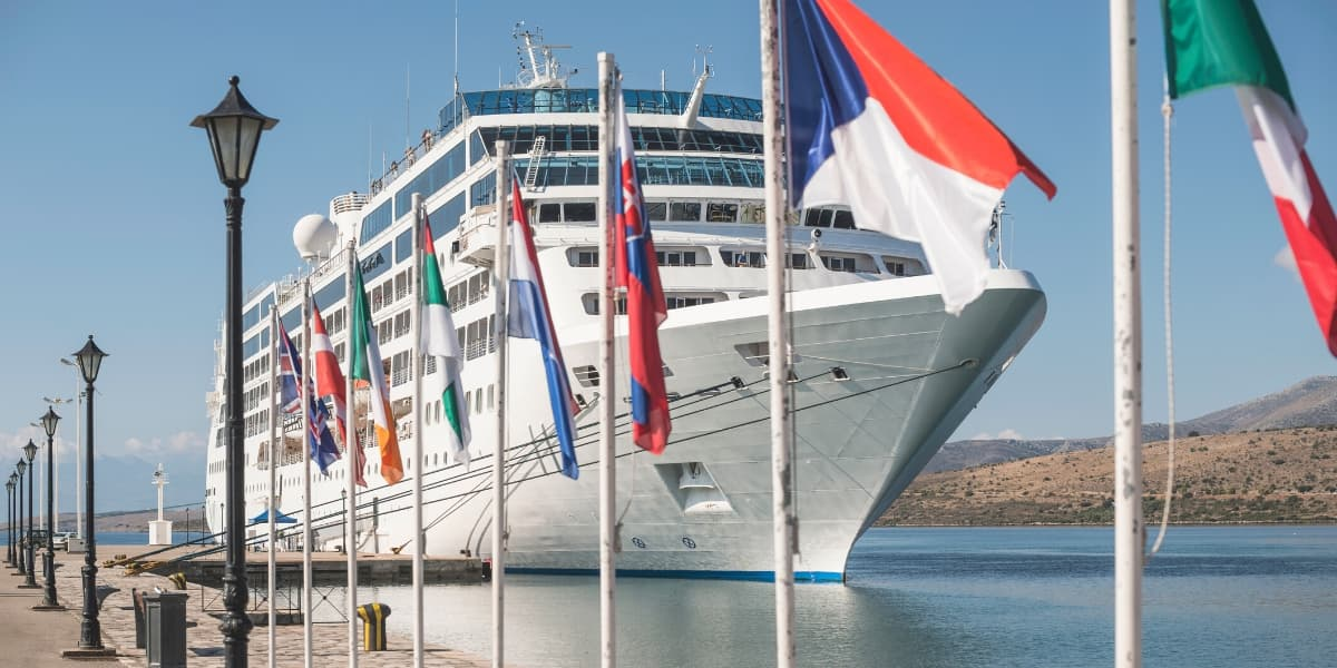 Cruise ship at a dock with several flags