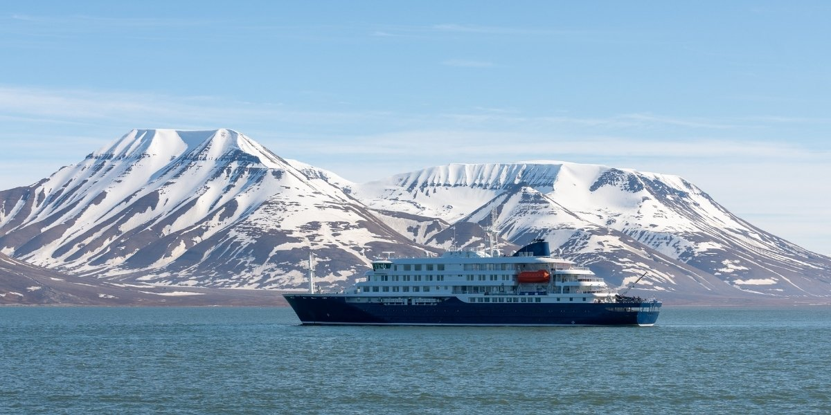 an expedition cruise ship with a backdrop of snow-capped mountains