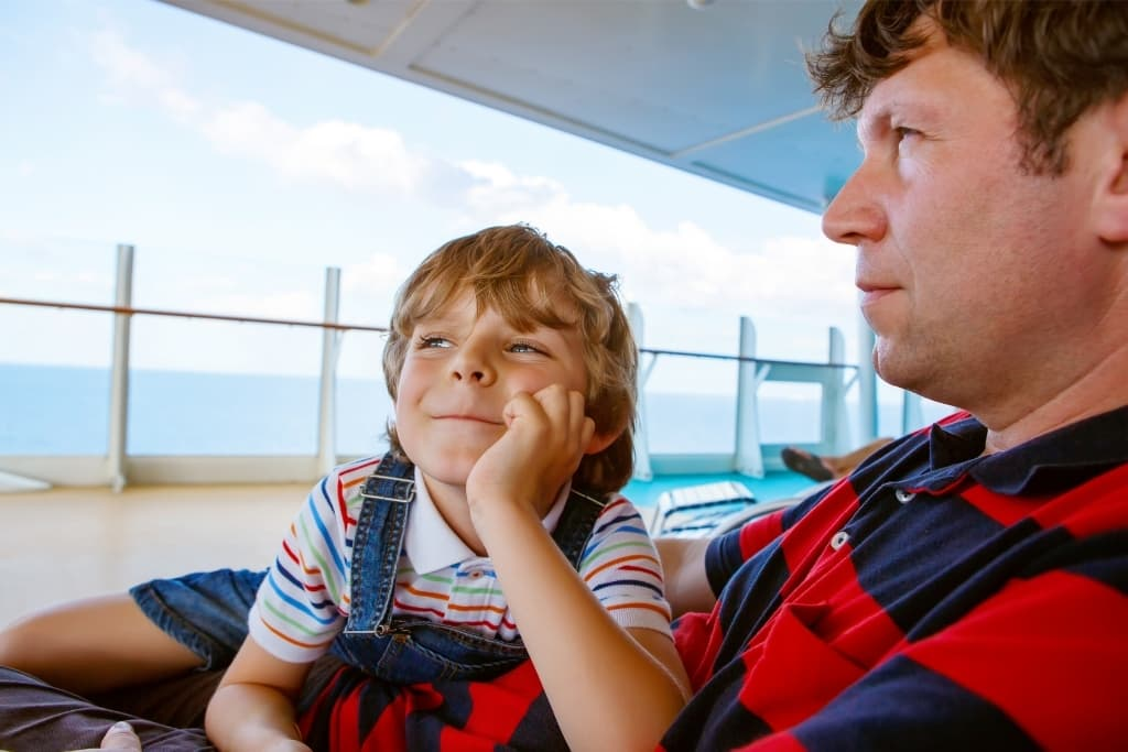 a little boy and his dad relaxing on a cruise ship deck